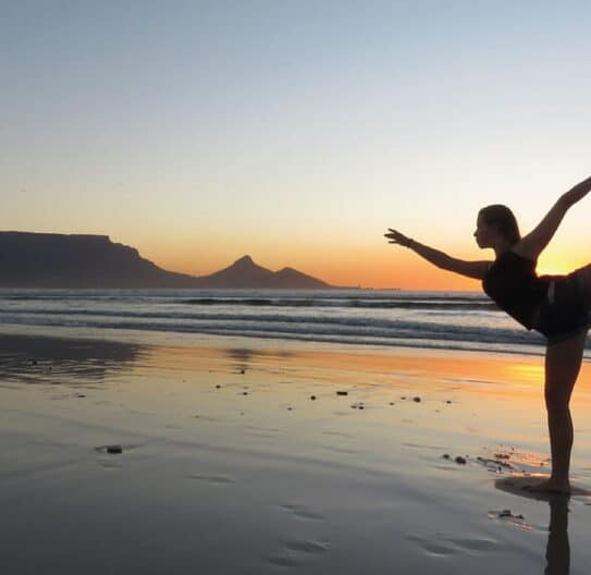 pige står på 1 ben på stranden
