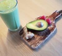 grøn smoothie og bræt med avokado og bær