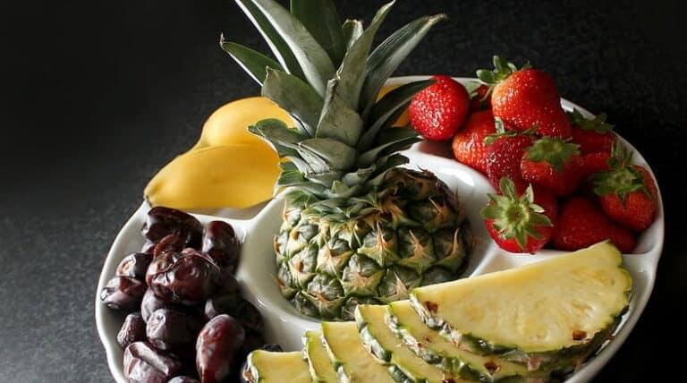 Skål med ananas, jordbær, bananer og dadler
