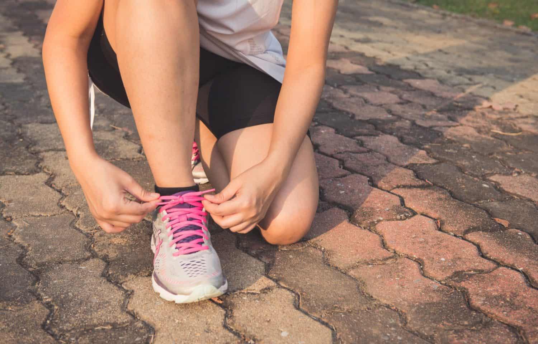pige med sorte shorts binder sine lyserrøde sko