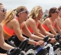 kvinder i rød toppe på motionscykler