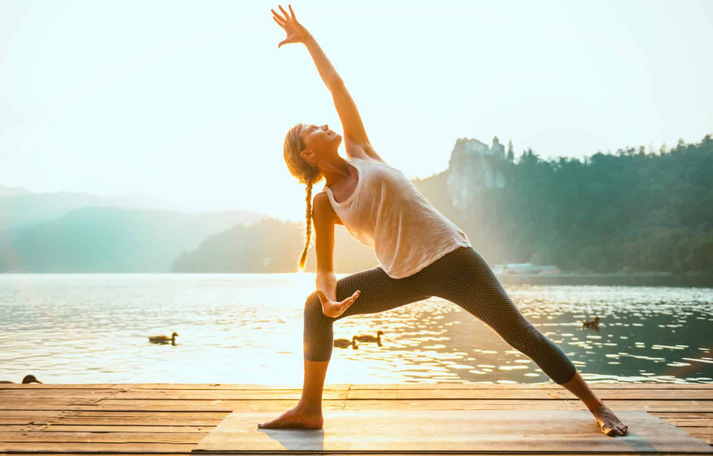 veltrænet pige laver yoga øvelsen trekanten